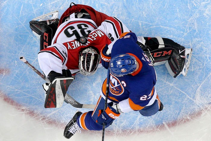 The puck comes to rest between the shoulder blades of Carolina Hurricanes goalie Curtis McElhinney (35) as he defends the crease against New York Islanders left wing Anders Lee (27) during the third period of game two of the second round of the 2019 Stanley Cup Playoffs on Sunday, April 28, 2019 at Barclays Center in Brooklyn. The Hurricanes defeated the Islanders 2-1 to take a 2-0 lead in the best-of-seven series.